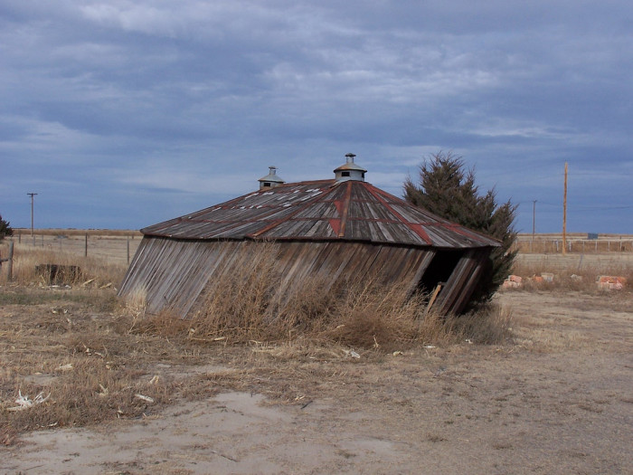 An old oval barn fights to stay upright.