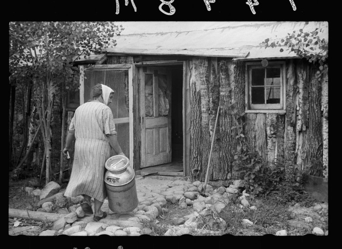 3. This is Mrs. Howard in 1939 bringing a milk can into her home. She and her daughter built the one room home themselves in Aitkin County.