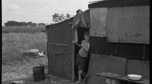 Son of a migrant family in the doorway of his temporary home near Winter Haven, Florida