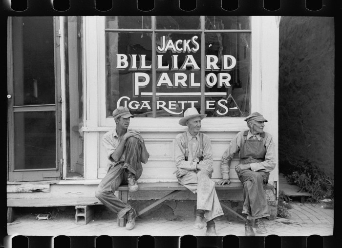 1. These farmers sit and visit out front of Jacks Billiard Parlor in Collins.