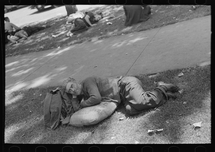 14. In August of 1937 in Minneapolis, a man rests on a sack of scratch seed in the park. You can see others behind him doing the same.