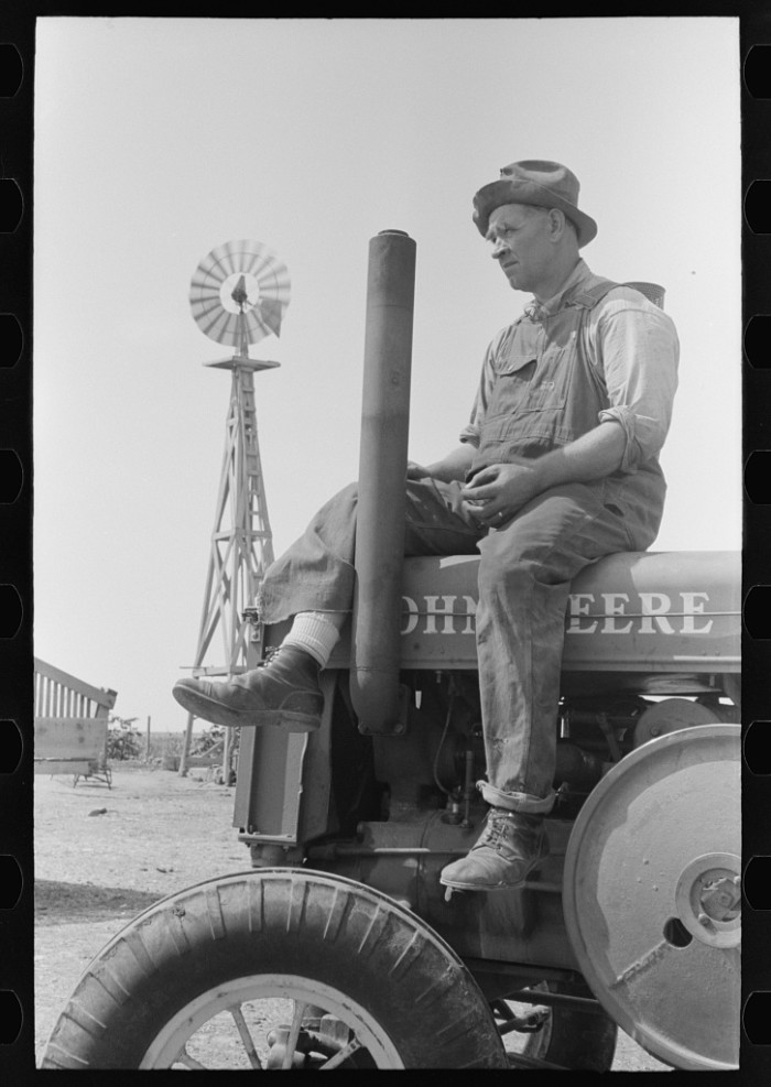 """14. """"Mr. Germeroth, Farm Security Administration client sitting on tractor which was bought by means of FSA loan."""""""