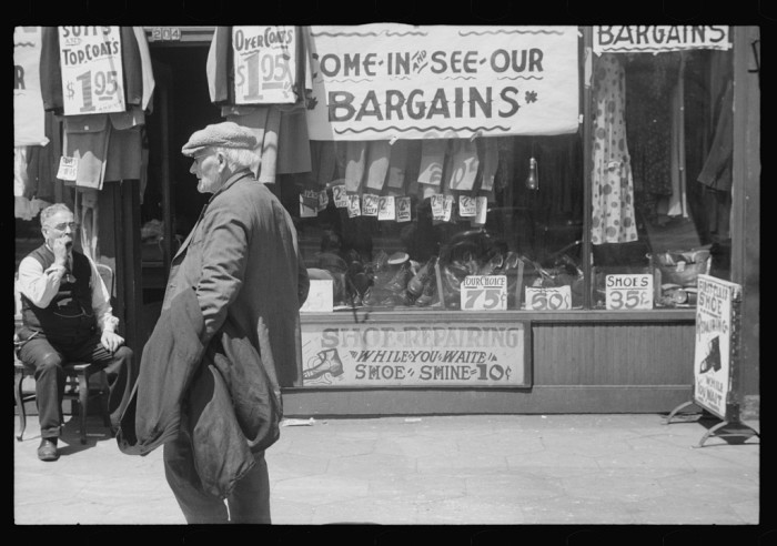 19. In 1937 Minneapolis, a man stands in front of a secondhand clothing store.