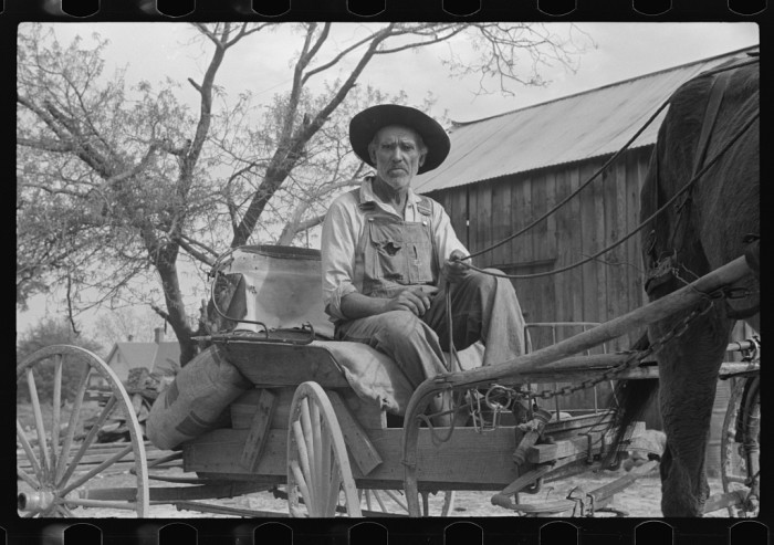 9. Lee Betties, rural rehabilitation client, leaving a general store with a sack of horse and mule feed on the back of his wagon in Woodville, Greene County, GA - May 1939