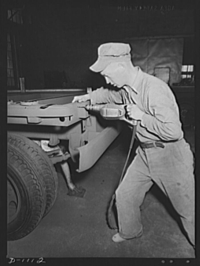 "12. ""Manufacture of semi-trailers for Defense transportation. These trailers are eqipped with a combination platform stake body and are intended for general use in Army camps and depots. They carry a payload of 7,000 pounds. This worker is attaching reflectors to the rear of the trailer frame."""