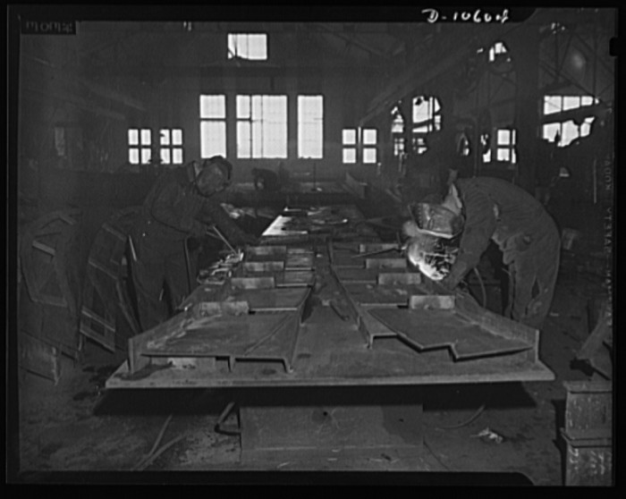 "14. ""The interior of a shipbuilding plant, showing men working with acetylene torches."""