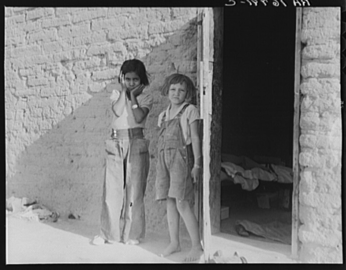 13. A couple of farmworkers' children mingle outside housing in 1937 near Chandler.