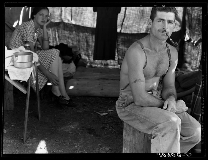 """23. """"Unemployed lumber worker goes with his wife to the bean harvest. Note social security number tattooed on his arm."""""""