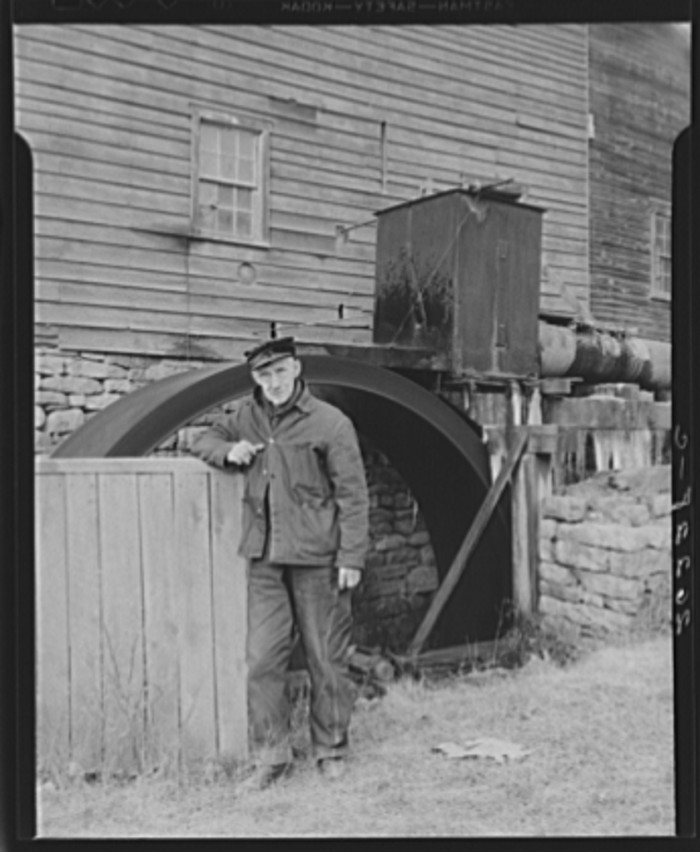 14. A resident of Chaneysville stands in front of a grist mill that is still in operation today.