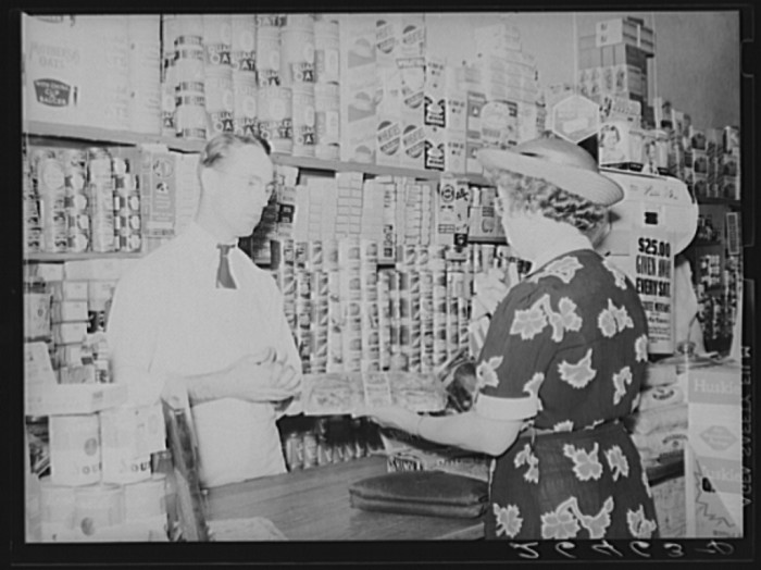 14. This one is a picture of a woman buying groceries at a grocery store in Blankenship in 1938.