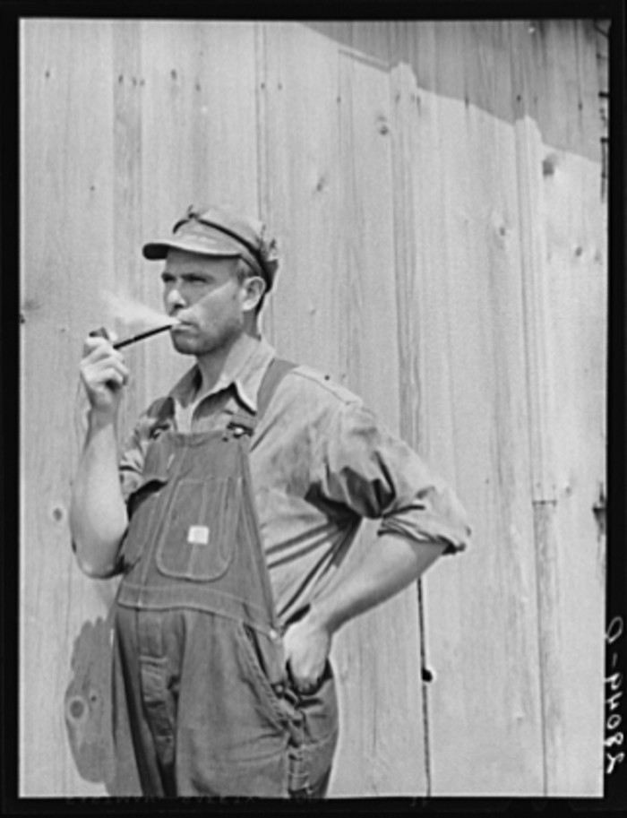 5. A farmer in Jasper County takes a break from the day's work to smoke tobacco from his wooden pipe.