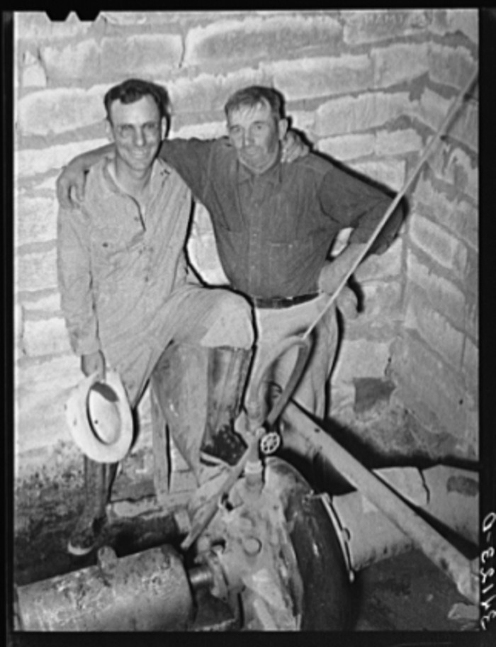 """2. """"Mr. Johnson and Mr. Wright, owners and cooperators in irrigation well on farm near Syracuse, Kansas. They are FSA (Farm Security Administration) clients."""""""