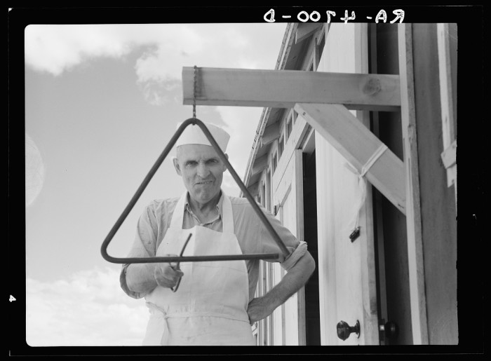 """19. """"The chef at the Rimrock Camp in the central Oregon land development project gets ready to go into action on the dinner gong. Oregon."""""""