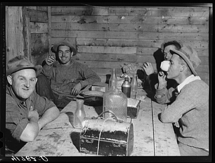 8. Workmen at the Woodman Potato Company just finishing lunch in a small room at the store house that serves as a lunchroom. (Caribou, 1940)