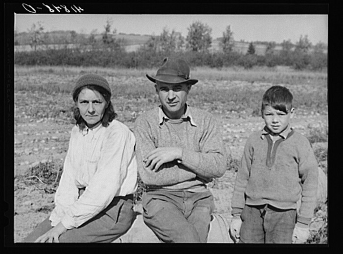 12. Very often entire families would become part of a large crew of potato pickers. This mother, father and son are taking a break during their lunch hour in a field. (Caribou,1940)