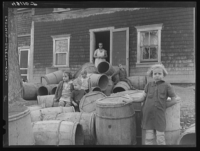 23. Children of Baptiste Deprui, French-Canadian potato farmer. Deprui ran a small seed foundation unit and also raised some certified seed oats. The barrels in front of the house were left there after he had stored all the potatoes in the cellar of the house. The potatoes completely filled the cellar as high as the floor boards. (Soldier Pond, 1940)