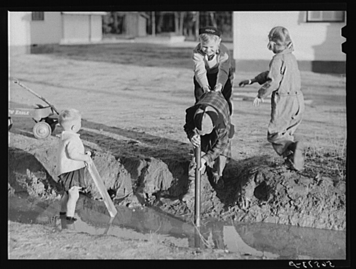 8. Children of Army men playing in water in front of their new house in Columbus, Georgia - December 1940