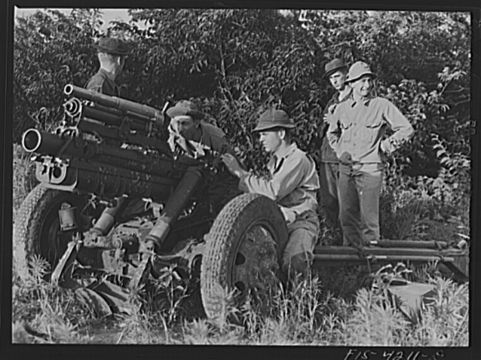 """11. """"Lining up guns during artillery practice. The small thirty seven mm gun mounted on the howitzer is used only in training."""""""