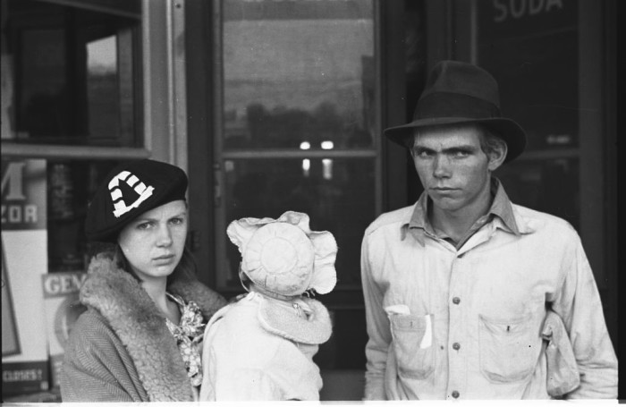 2. A family stands outside a shop in 1935. Their faces show the feeling of the era.