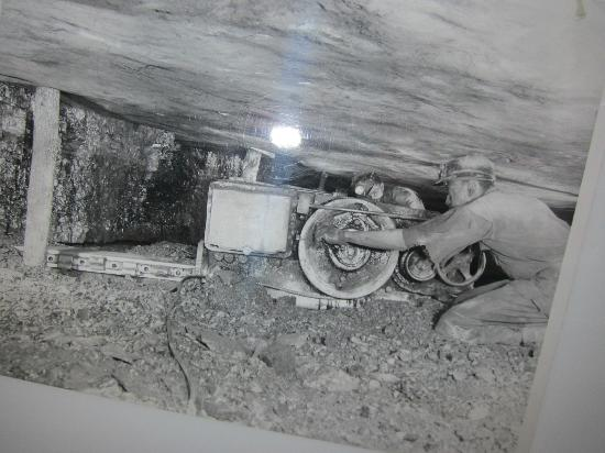 21. A miner working on some machinery in a mine, 1930.