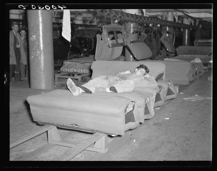 12) A young striker off of sentry duty is sleeping on an assembly line of auto seats at Fisher body plant No 3 in Flint, Jan 1937