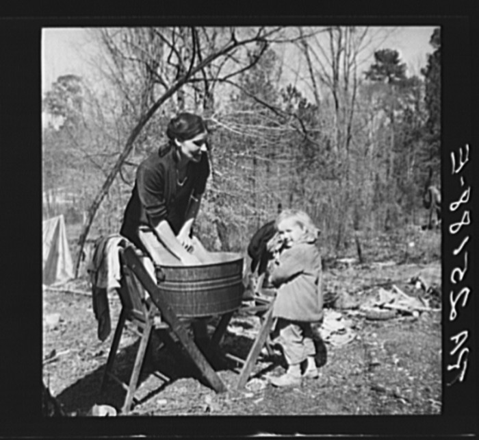 20. A mother washing clothes in a migrant camp, Birmingham - 1937.