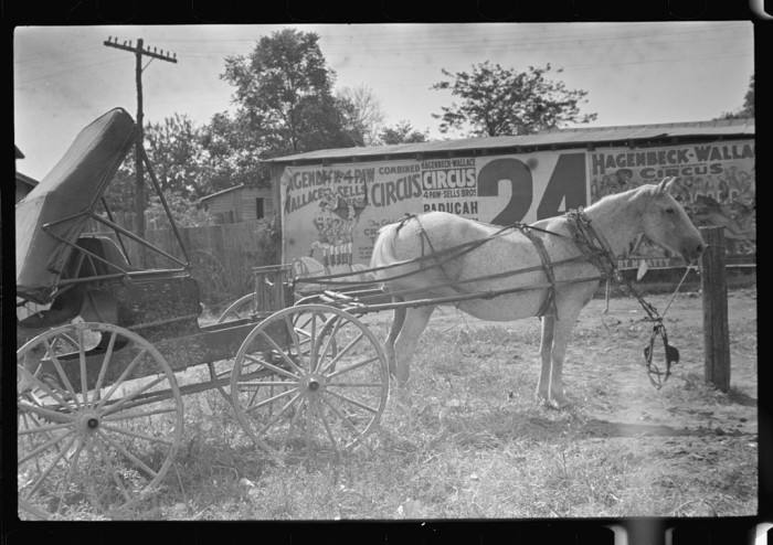 9. An empty buggy sits in front of a circus advertisement in 1935.