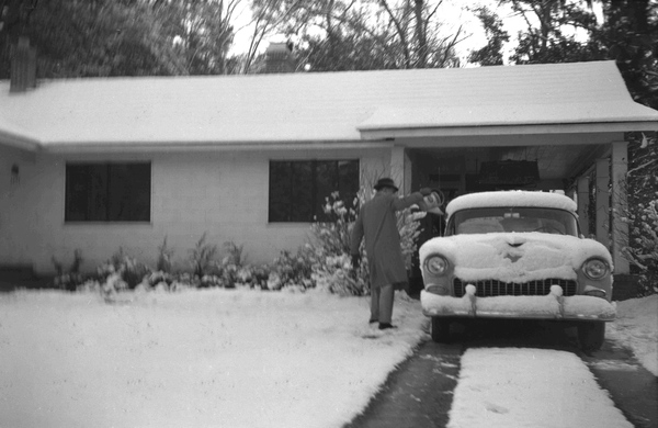 Frank H. Stoutamire clearing snow off his car