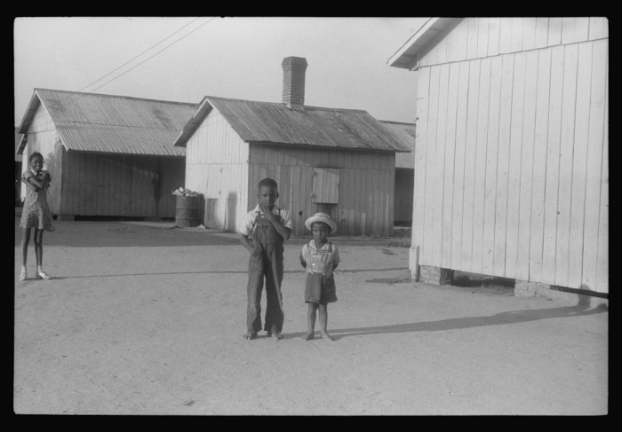 17. Young children of migrant families stand outside within the confines of the migrant barracks, 1940.
