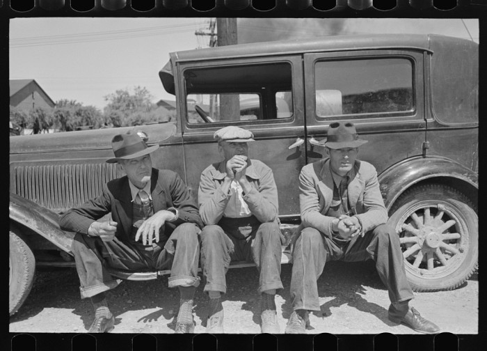 11. Farmers relaxing on the running board of a car while waiting in a liquid feed loading station in Owensboro, 1938.
