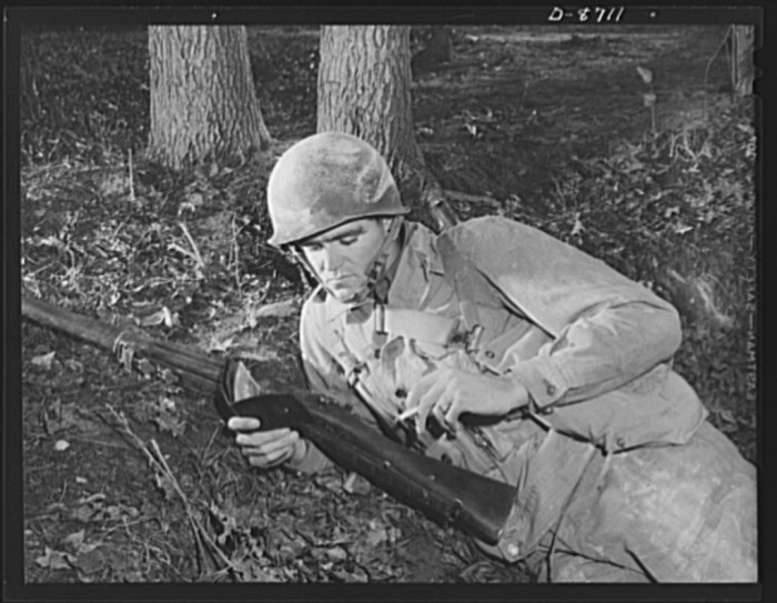 7. An infantryman takes a break from training to look at photos of his family kept in a wallet, November 1942.