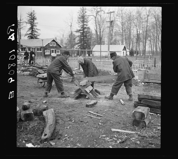 4) Members of a transient camp saw up old sleds for firewood near Hagerman Lake, April 1937.