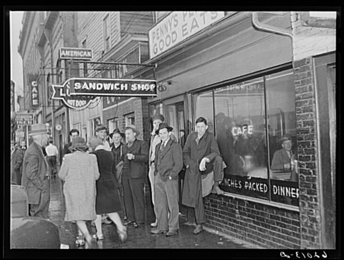 8. Men wait outside a local sandwich shop for the shift change at the powder plant, 1940.