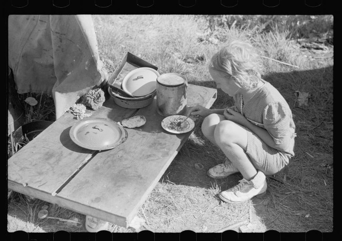 4) Migrant child eating in front of tent home, Berrien County, July 1940.