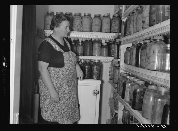 14. Mrs. Marinus Hansen of Box Elder County, shows off her shelves of home-grown canned goods.