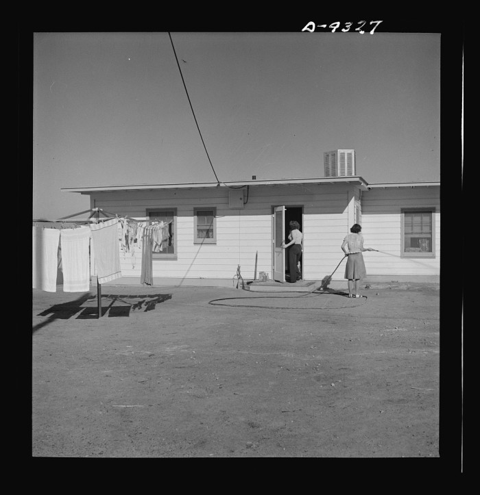 10. A magnesium production worker's wife waters the newly planted lawn around her Las Vegas home - 1943.