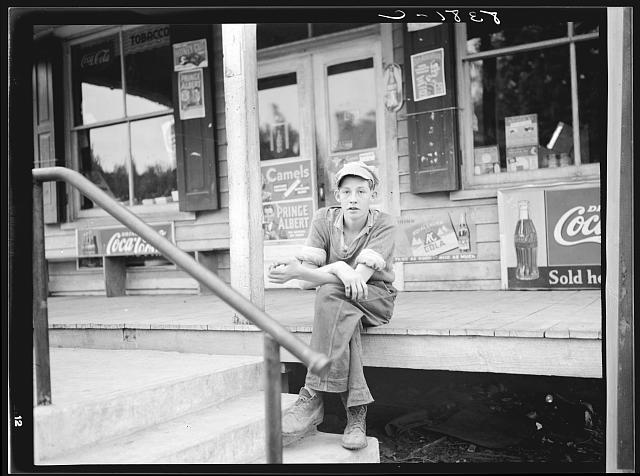 2. A young Nelson County boy sits on the porch of a general store in Roseland, 1938.