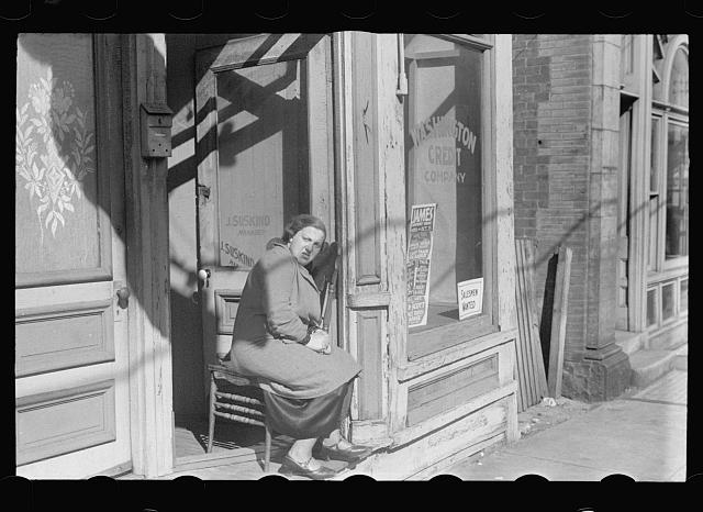 20. A woman huddles in the doorway of a decrepit storefront in Newport News, 1937.