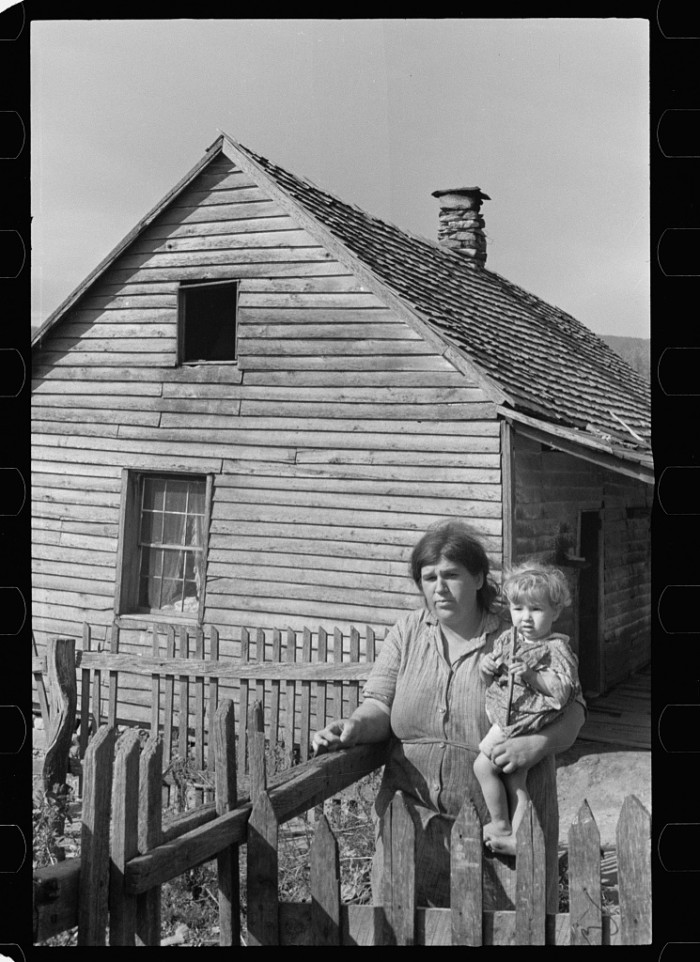 8. THEN: The mother of a family about to be relocated after the Shenandoah National Park was formed stands outside her home near Old Rag Mountain in Madison County, 1935