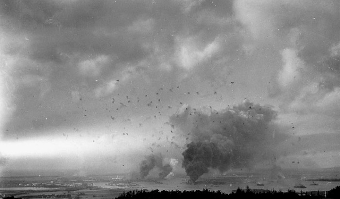 This panoramic view of Pearl Harbor during the Japanese raid features anti-aircraft shell bursts overhead, and was taken from the hills behind the harbor.