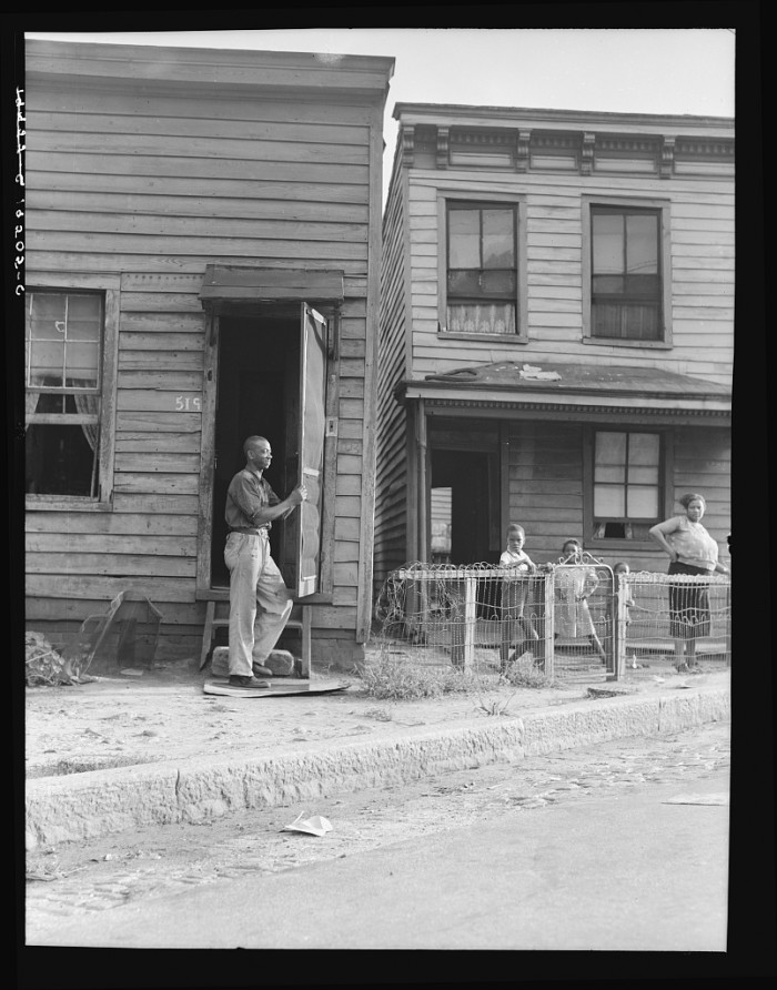 5. Families in Richmond stand outside their homes, 1938.