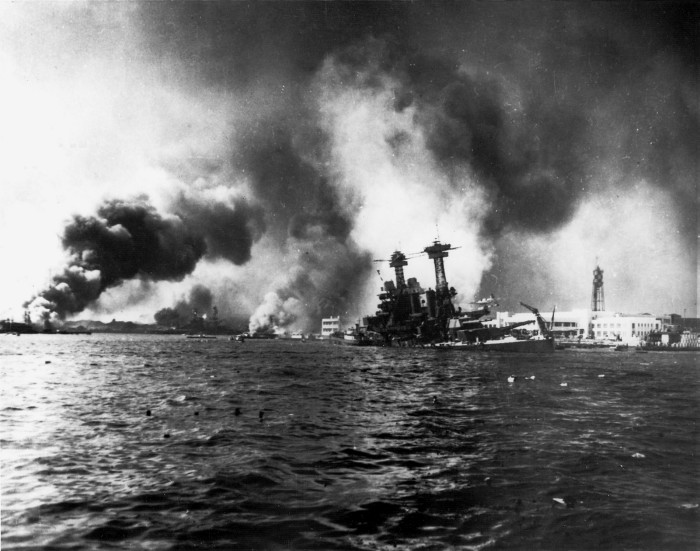 The USS California battleship slowly sinking near Ford Island, with the USS Shaw burning in the floating dry dock in the left distance. The USS Nevada is beached in the center-left.