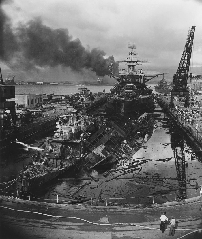 The USS Cassin, a destroyer, has capsized against the USS Downes, another destroyer, in a Pearl Harbor drydock. The USS Pennsylvania is astern, occupying the rest of the dry dock.