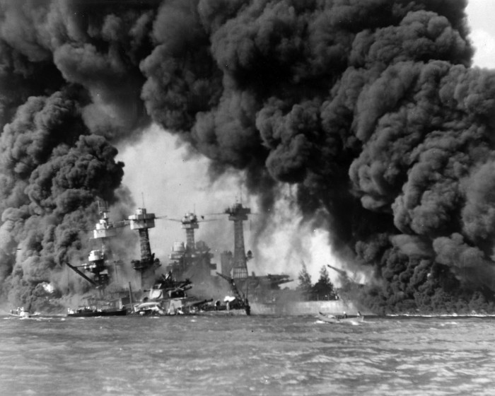 Two United States Navy battleships, the USS West Virginia and the USS Tennessee, are shrouded in smoke following the Japanese air raid.