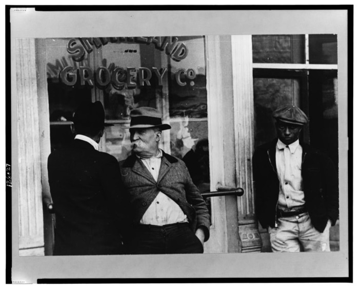 19. Unhappy faces take a smoke outside a local grocery in 1935.