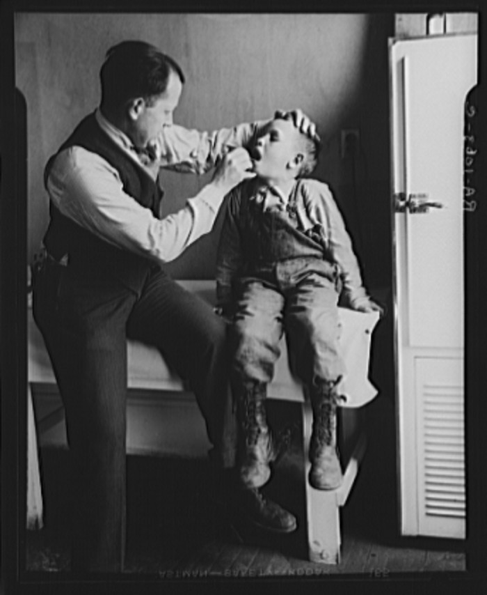 14. Here, a doctor examines the throat of a young boy in Reedsville.