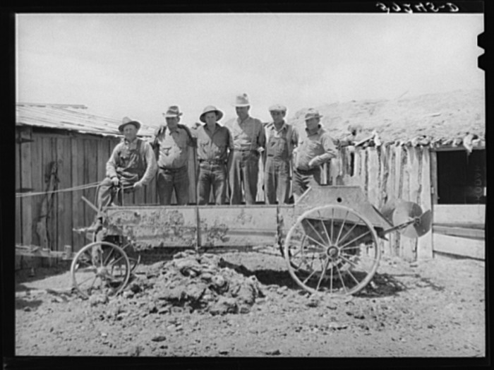 12. Farmers posing with a manure spreader.