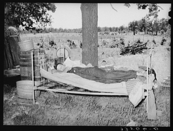 11. This migrant agricultural worker is napping on his bed outside his home in McIntosh County in 1939.