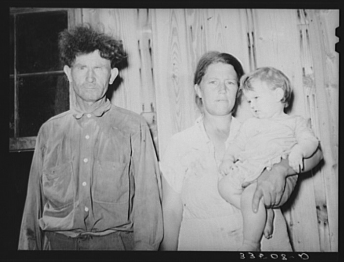 """12. This agricultural day laborer was a former oil field worker and miner. He is photographed with his wife and baby in McIntosh County in 1939.  He was quoted saying, """"I hope the next time you see me, you'll find me in better condition."""""""