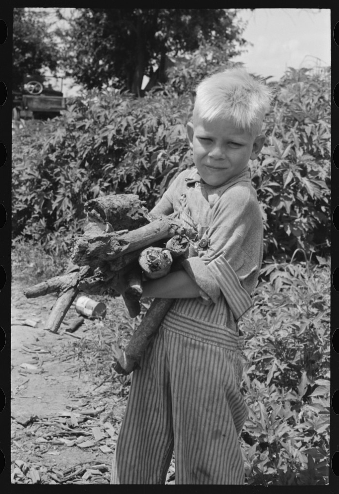 17. This boy was a son of a day laborer. He was carrying a load of wood in his arms near Webbers Falls in 1939.